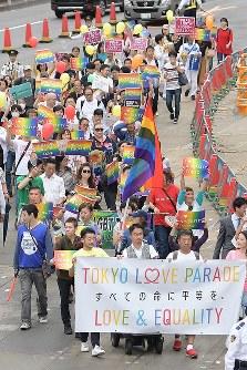 虹色のプラカードを掲げながら行進する「東京ラブパレード」の参加者ら=東京都新宿区で2018年10月8日午後3時54分、渡部直樹撮影