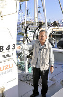請戸漁港で自分の漁船に乗る高野一郎さん=福島県浪江町で