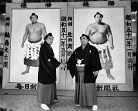 毎日新聞社から贈られた優勝額の前でガッチリ握手する北の湖(右)と輪島=東京・蔵前国技館で1976年