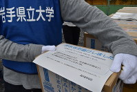 One of the boxes of bottled water delivered to residents of temporary housing and an explanatory paper detailing the combined project between Iwate Prefectural University, Ohio University, Chubu University and the Honjo International Scholarship Foundation is pictured near the grounds of Yokota Elementary School, in Rikuzentakata, Iwate Prefecture, on Sept. 29, 2018. (Mainichi/Alina Kordesch)