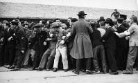昭和天皇を一目見ようと集まった人々を警官がおさえようとしている=1947年12月5日撮影、アレクサンダー・ターンブル図書館所蔵