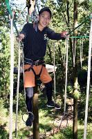 足元が不安定な輪に足をかけながら進むスタッフ=奈良県山添村三ケ谷の「冒険の森inやまぞえ」で、佐藤英里奈撮影