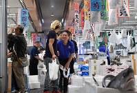 Yasuhiro Yamazaki, right, president of intermediate wholesaler Yamaharu, smiles as he bows to a customer at the newly opened Toyosu market in Tokyo's Koto Ward on Oct. 11, 2018. (Mainichi/Kimi Takeuchi)