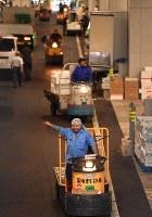 豊洲市場が開場し知人に笑顔であいさつする小型運搬車を運転する男性=東京都江東区で2018年10月11日午前3時58分、宮間俊樹撮影