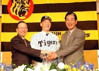 阪神にFA移籍し、星野監督(右)、野崎球団社長(左)と握手する金本=2002年11月22日、三村政司撮影