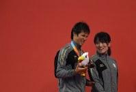 【アジアパラ大会・競泳】男子100メートル背泳ぎ(視覚障害S11)で金メダルを獲得し、表彰式で笑顔を見せる木村敬一(左)=インドネシア・ジャカルタで2018年10月11日、久保玲撮影