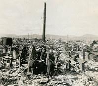 広島瓦斯広島工場付近に立つ少女。機械や煙突が見える=1945年秋ごろ撮影、アメリカ海兵隊歴史部所蔵