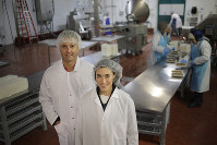 In this Oct. 2, 2018, photo Ollie co-founders Gabby Slome and Alex Douzet pose for a picture at the manufacturing facility where their dog food is made in Woodbridge, N.J. (AP Photo/Seth Wenig)