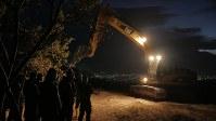 夕闇の中、共同墓地に埋葬された遺体の前で祈りをささげる国軍兵士ら=インドネシア・中スラウェシ州パルで2018年10月10日、モハマド・ファズルル撮影