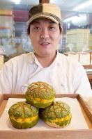 「かぼちゃメロンパン」を手にする丸久晃さん=奈良県生駒市で、熊谷仁志撮影