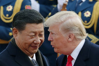 In this Nov. 9, 2017 file photo, U.S. President Donald Trump, right, chats with Chinese President Xi Jinping during a welcome ceremony at the Great Hall of the People in Beijing. (AP Photo/Andy Wong)