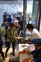 豊洲市場の一般公開が始まり、水産仲卸売場棟の入り口で見学者カードを受け取る人たち=東京都江東区で2018年10月13日午前9時57分、竹内紀臣撮影