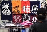 一般公開が始まり、にぎわう豊洲市場の魚がし横町には色々なTシャツも=東京都江東区で2018年10月13日午前11時51分、竹内紀臣撮影