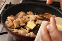 フライパンにオリーブ油とみじん切りのニンニクを熱し、エリンギを炒め、エビを加えて塩・コショウをふり色が変わるまで炒めたらバターを加える=根岸基弘撮影