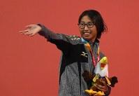 女子200メートル自由形(知的障害S14)で優勝し、声援に応える北野=インドネシア・ジャカルタで7日、久保玲撮影