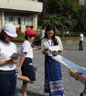 運動場で多言語放送の練習をする子どもたち。アナウンスの上達が遅れているため、ボランティアがサポートに入った=横浜市南区で
