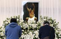 輪島さんの愛用品や写真が飾られた献花所で手を合わせる人たち=東京都港区の青山葬儀所で2018年10月15日午前10時12分、佐々木順一撮影