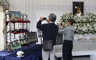 輪島さんの愛用品や写真が飾られた献花所を訪れた人たち=東京都港区の青山葬儀所で2018年10月15日午前10時12分、佐々木順一撮影