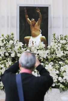 輪島さんの愛用品や写真が飾られた献花所を訪れた人たち=東京都港区の青山葬儀所で2018年10月15日午前10時14分、佐々木順一撮影
