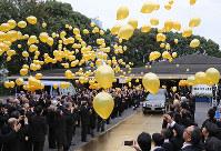 元横綱・輪島さんのひつぎを乗せた車の前で、金色の風船を飛ばす参列者=東京都港区の青山葬儀所で2018年10月15日午後0時41分、佐々木順一撮影