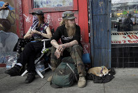 In this Oct. 1, 2018 photo, Stormy Nichole Day, left, sits on a sidewalk on Haight Street with Nord (last name not given) and his dog Hobo while interviewed about being homeless in San Francisco. (AP Photo/Jeff Chiu)