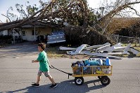Anthony Weldon, 11, pulls a cart with his family's belongings as they relocate from their uninhabitable damaged home to stay at their landlord's place in the aftermath of Hurricane Michael in Springfield, Florida, on Oct. 15, 2018. (AP Photo/David Goldman)