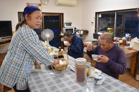 仕事帰りの工事関係者に夕食を提供する竹原伊都子さん(左)=熊本県南阿蘇村で、城島勇人撮影