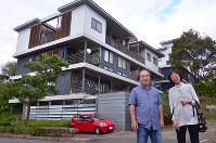 コーポラティブ住宅「つなね」の前に建つ山下好次さん(左)と田中智子さん=奈良市で、中津成美撮影