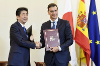 Japanese Prime Minister Shinzo Abe (L) and his Spanish counterpart Pedro Sanchez shake hands after signing an agreement in Madrid on Oct. 16, 2018. (Kyodo)