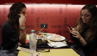 Giulia Terranova, left and Chiara Valenzano have lunch at the 'This is not a Sushi bar' restaurant, in Milan, Italy, on Oct. 16, 2018. (AP Photo/Luca Bruno)