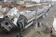 People gather after a train derailed on Oct.16, 2018 near Sidi Bouknadel, Morocco. (AP Photo/Abdeljalil Bounhar)