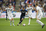 France's Kylian Mbappe, 2nd left, challenges for the ball with Germany's Toni Kroos, left, and Germany's Toni Kroos while Germany's Matthias Ginter, right, looks on during a UEFA Nations League soccer match between France and Germany at Stade de France stadium in Saint Denis, north of Paris, on Oct. 16, 2018. (AP Photo/Christophe Ena)