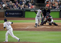 Boston Red Sox's Jackie Bradley Jr., right, watches his grand slam off Houston Astros relief pitcher Roberto Osuna during the eighth inning in Game 3 of a baseball American League Championship Series on Oct. 16, 2018, in Houston. (AP Photo/Lynne Sladky)