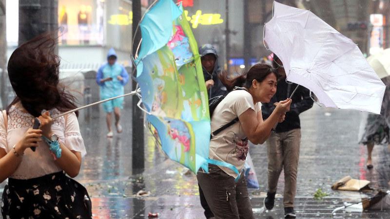 台風の強い雨風で傘を飛ばされそうになる人たち=大阪市中央区で2018年9月4日、幾島健太郎撮影