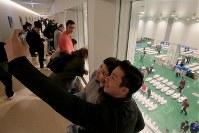 競りにかけられるマグロが並ぶ豊洲市場で記念撮影する外国人観光客=東京都江東区で2018年10月18日午前5時25分、和田大典撮影
