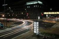 開場から1週間がたった豊洲市場の正門を通る車両の光跡。開場当初のような渋滞はほぼ解消されている。(長時間露光)=東京都江東区で2018年10月18日午前4時36分、和田大典撮影