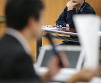 判決後の集会で弁護士(手前)の話を聞く被告の男性=神戸市中央区で、梅田麻衣子撮影