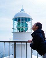不動まゆうさんが灯台めぐりでの写真撮影にお勧めする「灯台キス写真」。2018年3月2日に「室戸岬灯台」で撮影したもの=高知県室戸市室戸岬で、不動さん提供