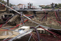 Residents of Trebes, southern France, look at a destroyed street the day after floods hit the town on Oct. 16, 2018. (AP Photo/Fred Lancelot)