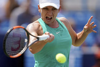 In this Aug. 19, 2018 file photo, Simona Halep, of Romania, returns to Kiki Bertens, of the Netherlands, during the finals at the Western & Southern Open tennis tournament in Mason, Ohio. (AP Photo/John Minchillo)