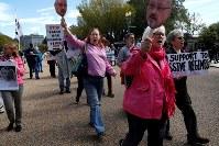 サウジアラビアのカショギ記者行方不明事件に抗議し、米ホワイトハウス周辺で抗議する人たち=19日、ロイター
