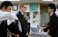 出発前の点呼をするウォルフガング・ルガーさん(中央)。「停車時はサイドとパーキングで完全停止」と担当者とともに声に出して確認し、車に向かった=東京都足立区で2018年10月18日、小川昌宏撮影