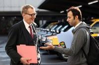 朝の出発前、先月から乗車するパキスタン人の運転手(右)と言葉を交わすウォルフガング・ルガーさん。「先輩」として乗客が拾いやすい場所の相談にのる=東京都足立区で2018年10月18日、小川昌宏撮影