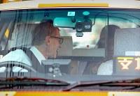 目的地に到着し、乗客から支払いを受け取り、笑顔で送り出すウォルフガング・ルガーさん=東京都内で2018年10月16日、小川昌宏撮影