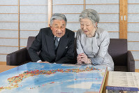 Emperor Akihito, left, and Empress Michiko examine a map of Japan with pins showing the places they have visited at the Imperial Palace in central Tokyo on Oct. 10, 2018. (Photo courtesy of the Imperial Household Agency)