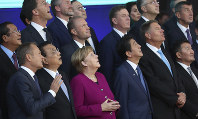 European Union and Asian leaders look up at a drone during a group photo during an EU-ASEM summit in Brussels, on Oct. 19, 2018. (AP Photo/Francisco Seco)