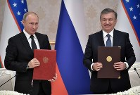 Russian President Vladimir Putin, left, and Uzbek President Shavkat Mirziyoyev pose after a signing ceremony during their meeting in Tashkent, Uzbekistan, on Oct. 19, 2018. (Pool Photo via AP)