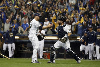 Milwaukee Brewers relief pitcher Corbin Burnes (39) and catcher Manny Pina (9) celebrate after Game 6 of the National League Championship Series baseball game against the Los Angeles Dodgers on Oct. 19, 2018, in Milwaukee. The Brewers won 7-2. (AP Photo/Jeff Roberson)