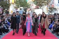 道路に特設されたランウエーを歩くDream Amiさん(中央)らモデルたち=東京都渋谷区で2018年10月21日午後2時7分、和田大典撮影