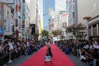 道路に特設されたランウエーを歩くモデルたち=東京都渋谷区で2018年10月21日午後1時37分、和田大典撮影